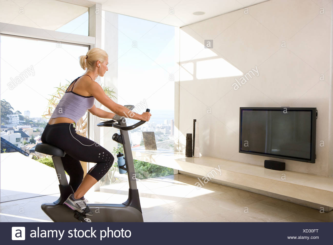 Mature woman riding stationary bicycle in living room, side view ...