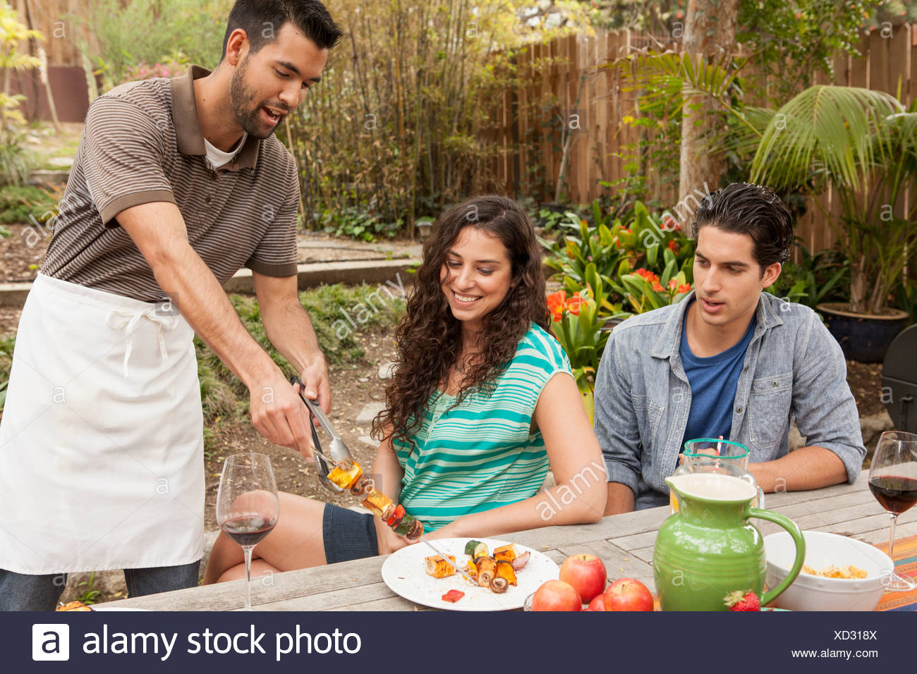 Friends sitting around table sharing barbecue food - Stock Image