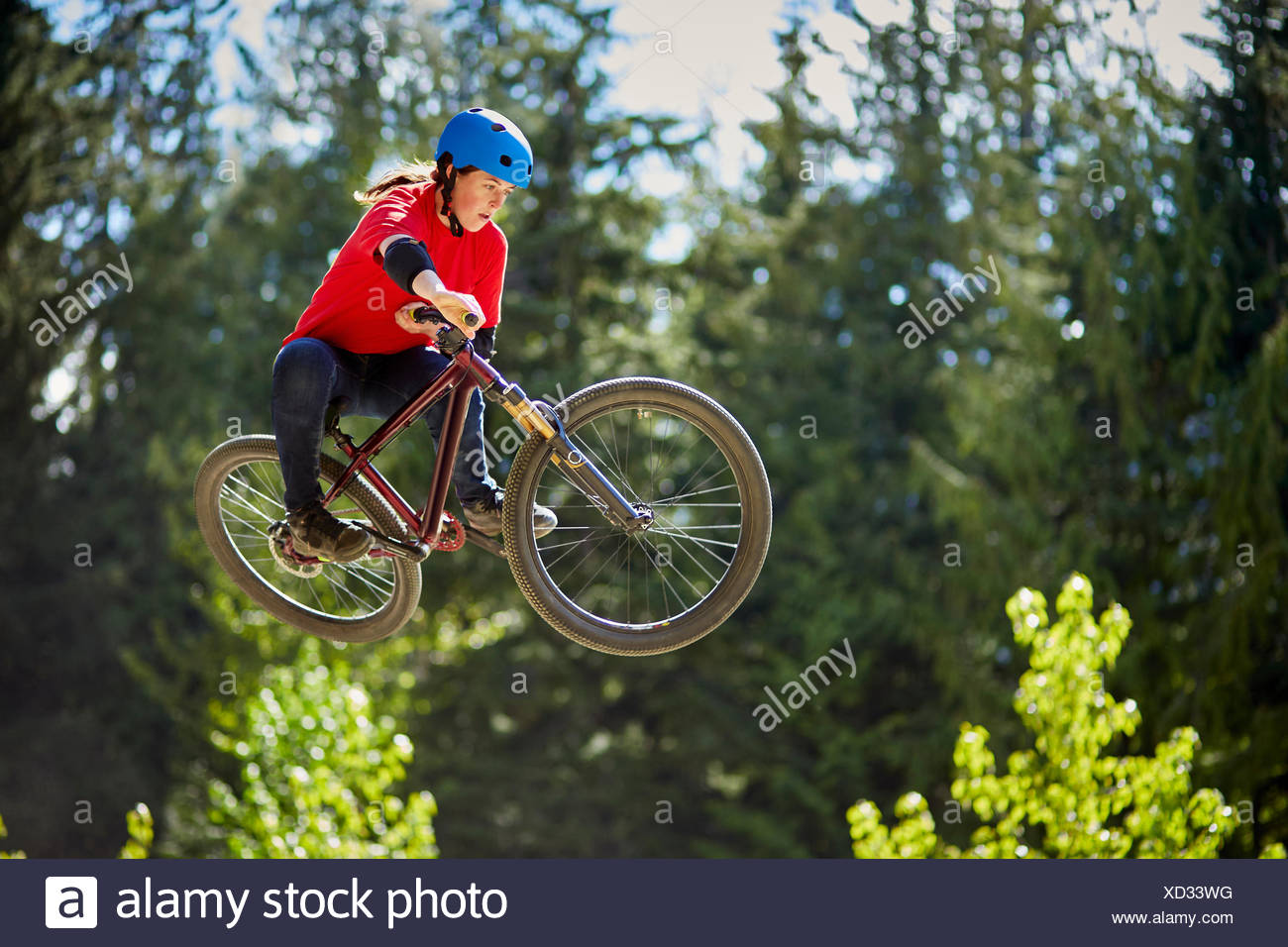 Young female bmx biker jumping mid air in forest - Stock Image