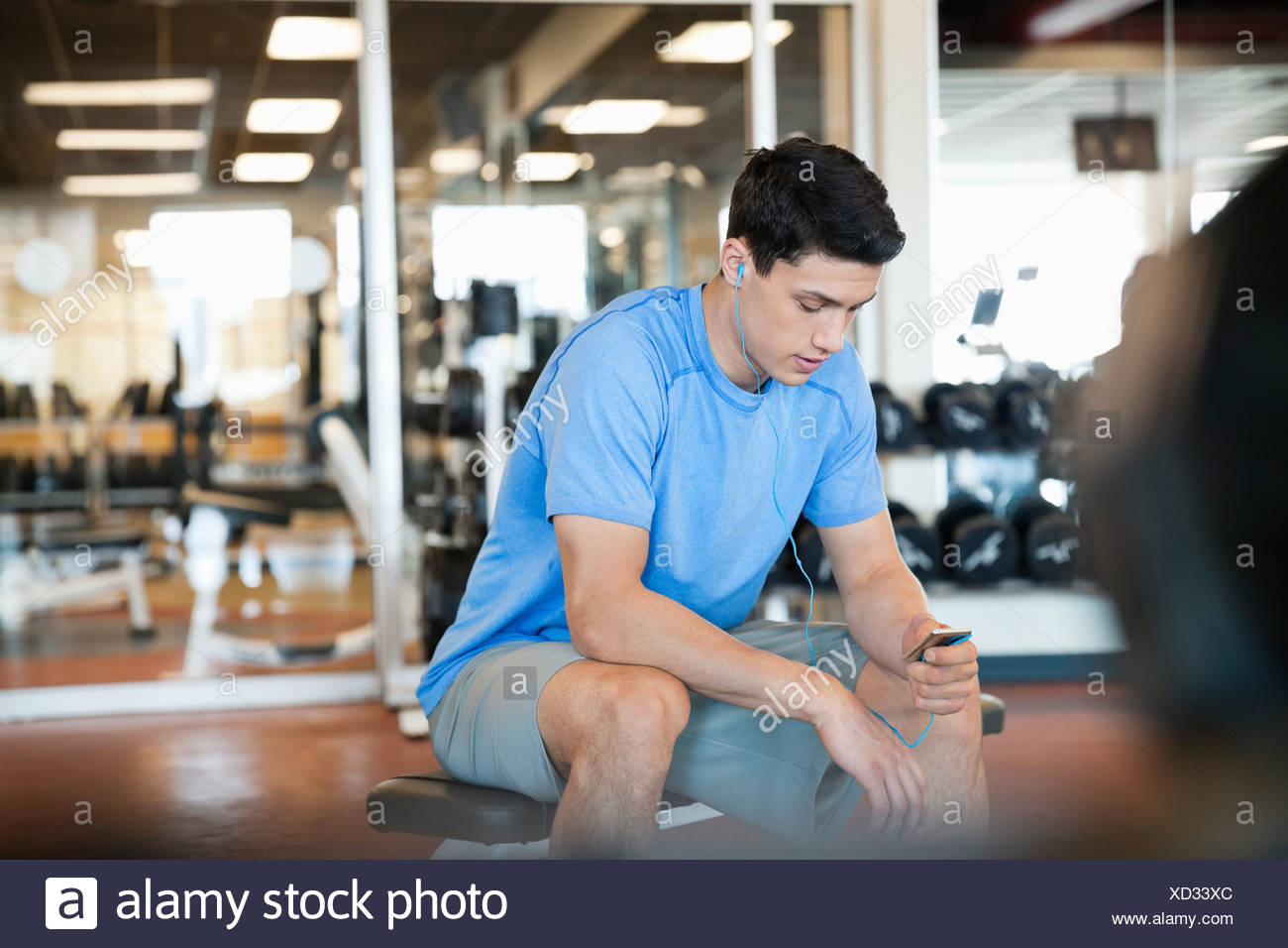 Man listening to music on earbuds at fitness center - Stock Image