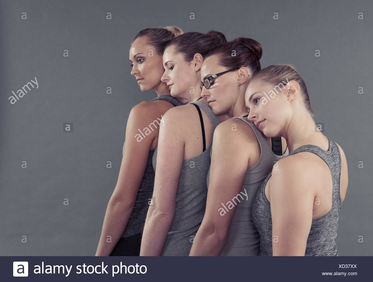 Young women in a row, leaning on each other,  grey background - Stock Image