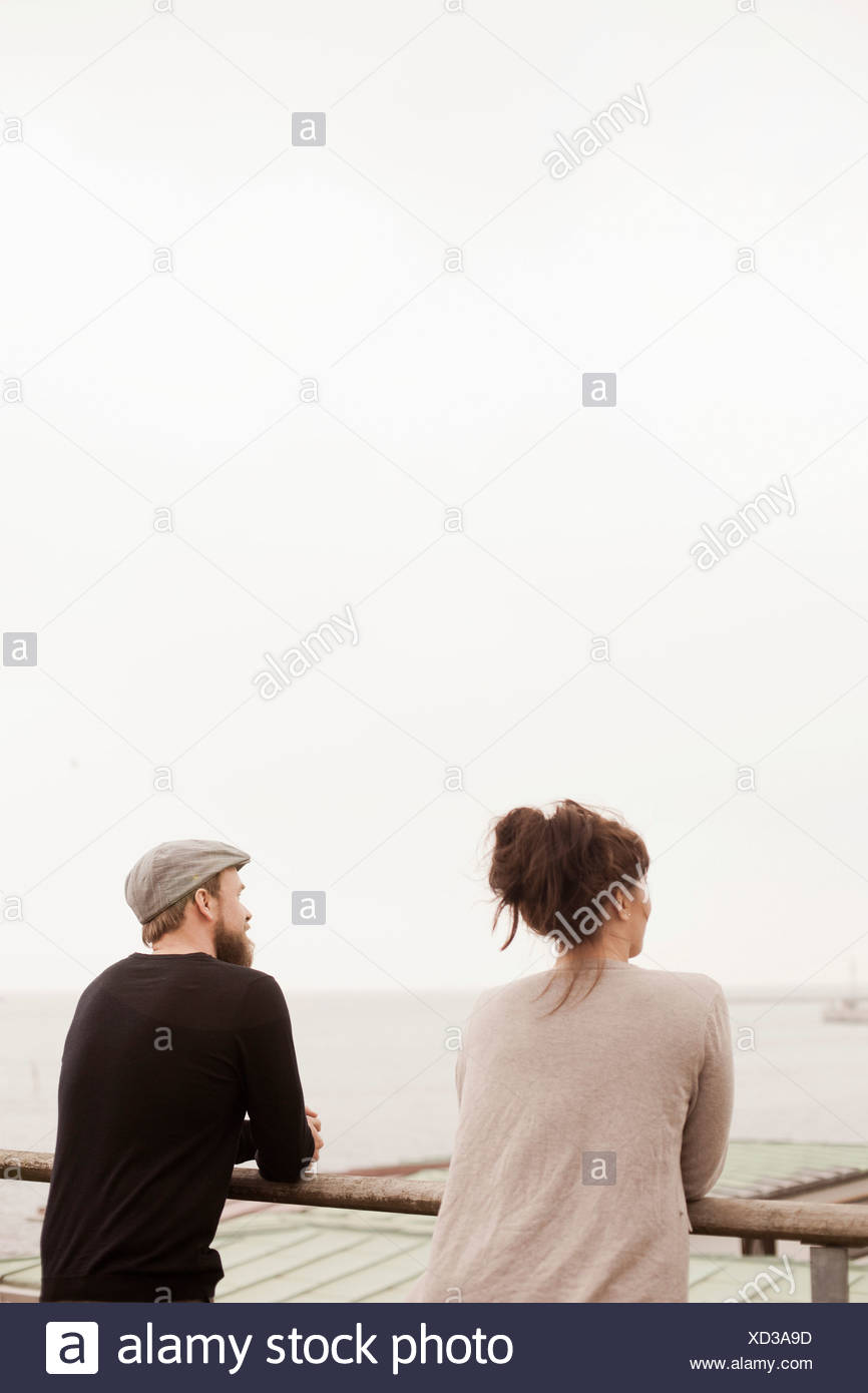 Rear view of business people standing by railing against clear sky - Stock Image