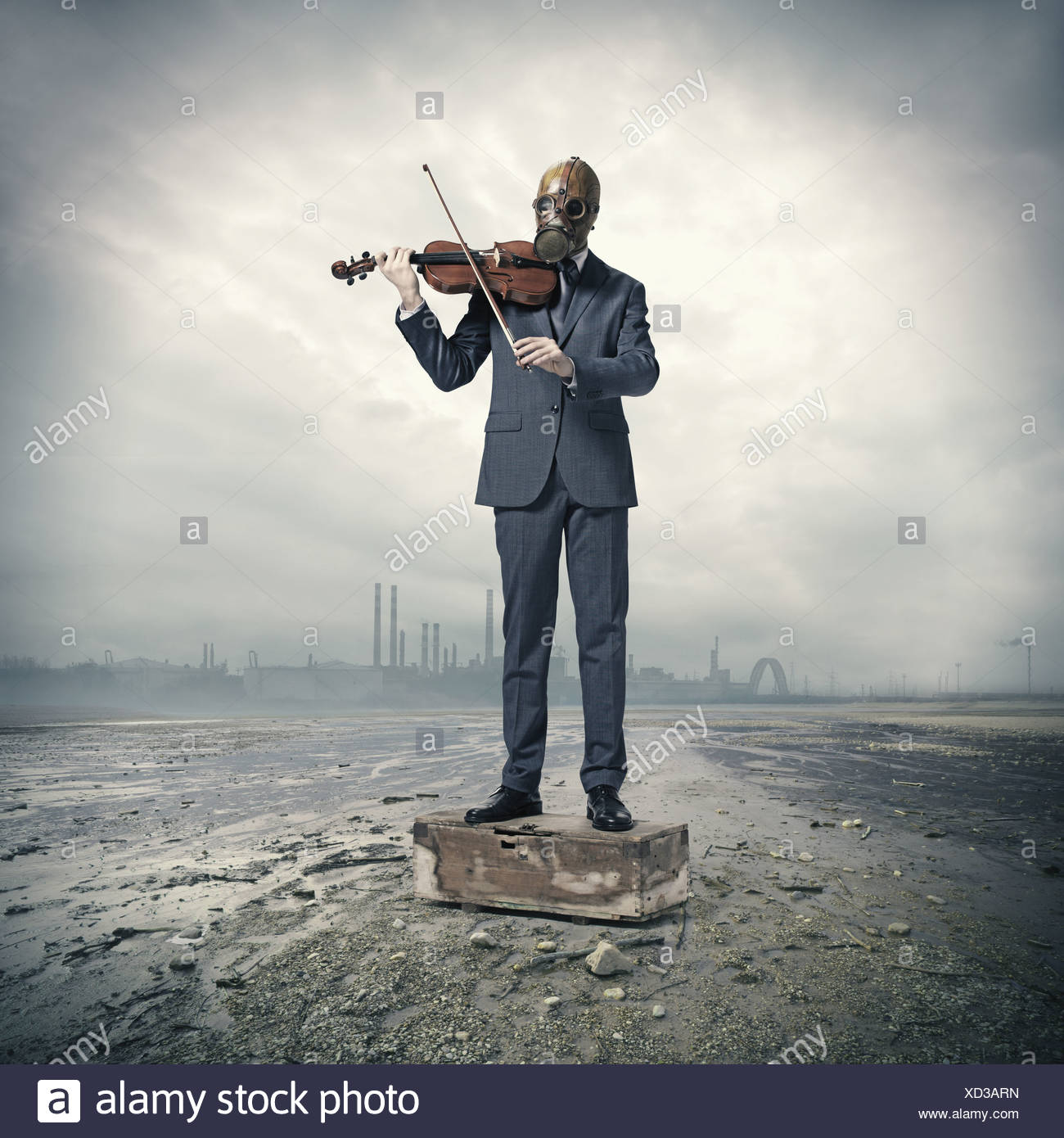 businessman with gas mask, plays the violin - Stock Image