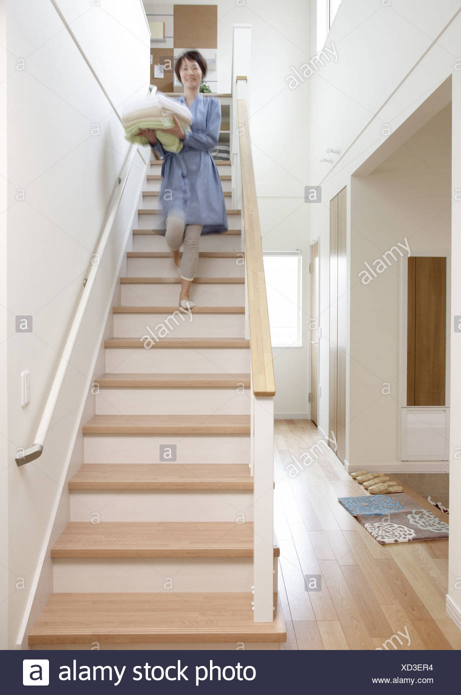 Woman downing stairs - Stock Image