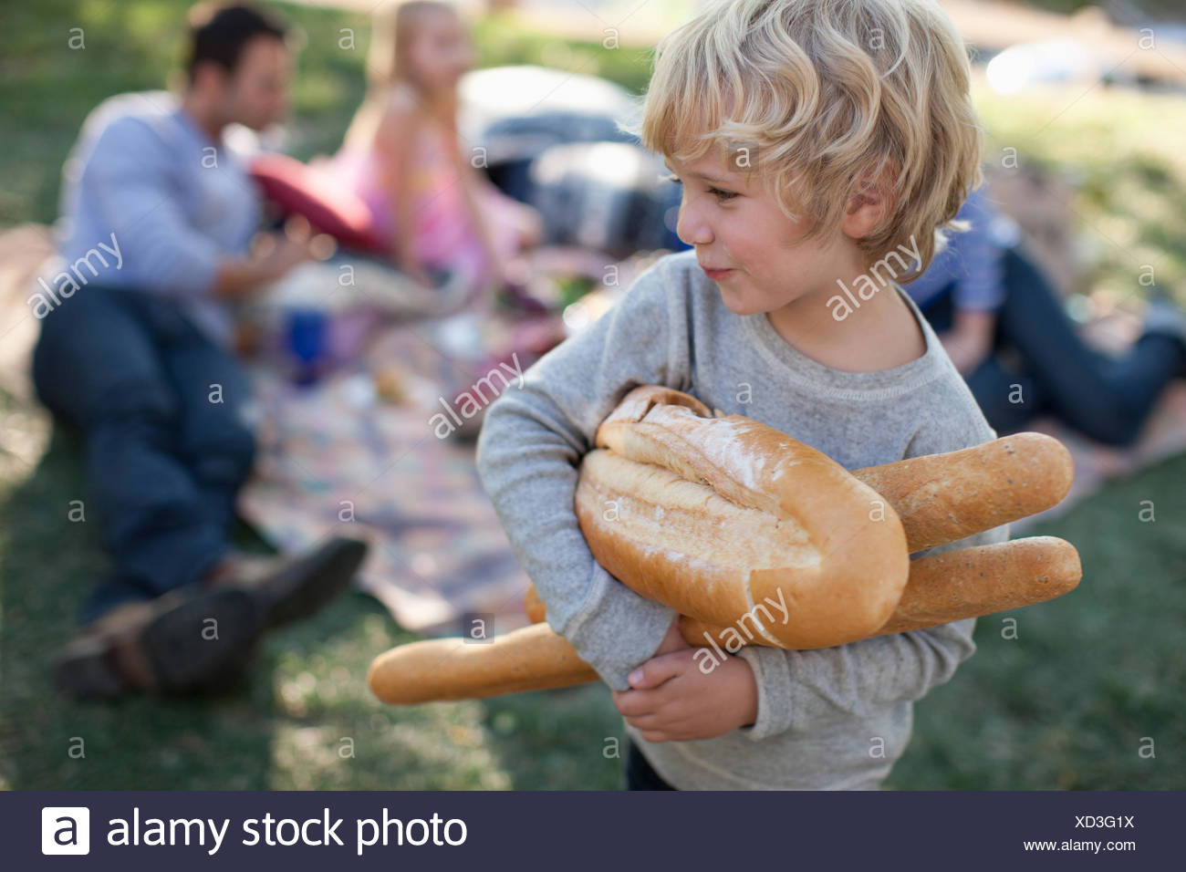 Boy holding loaves of bread outdoors - Stock Image