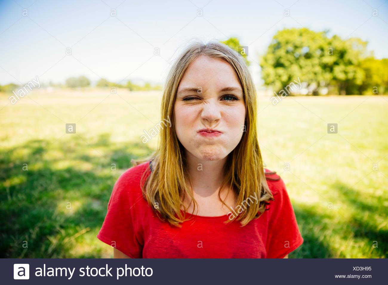 Portrait of teenage girl outdoors grimacing - Stock Image
