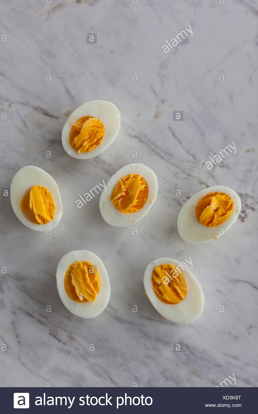 Hard-boiled eggs cut in half on the white marble surface - Stock Image