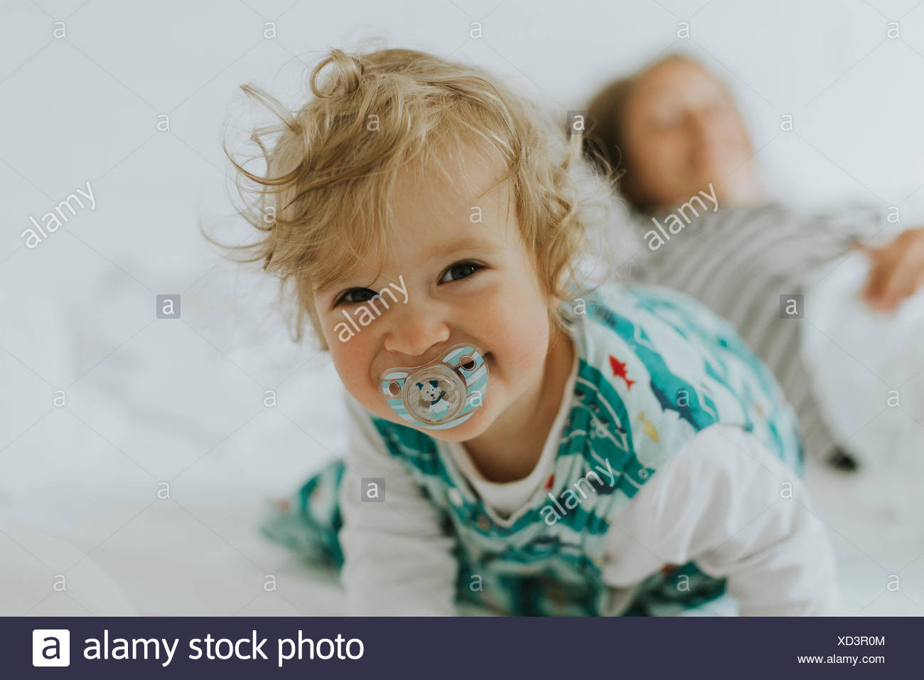 Portrait of happy little girl with mother in bed Stock Photo