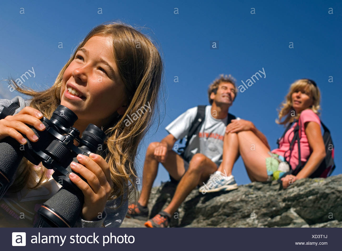 familiy on a mountain trail, girl with a field glass, France - Stock Image
