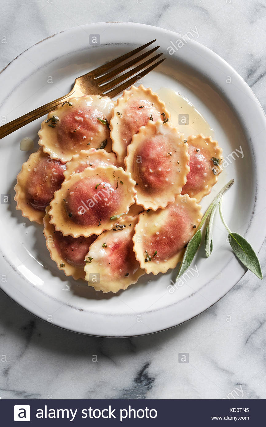 Beet & goat cheese ravioli with fresh sage and brown butter sauce. Plated with a gold fork on a marble surface. - Stock Image