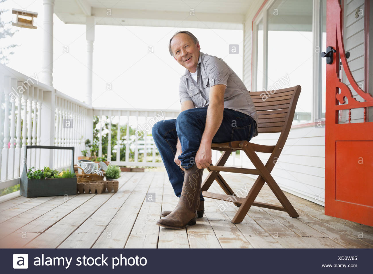 Man pulling on cowboy boots - Stock Image