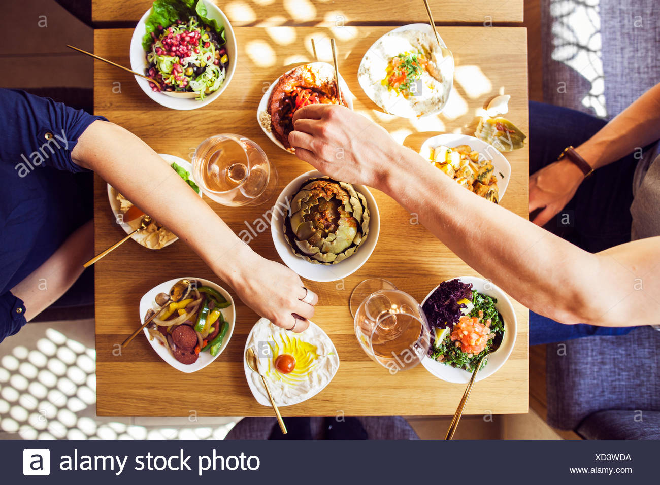 Directly above shot of couple eating meze at Lebanese restaurant - Stock Image