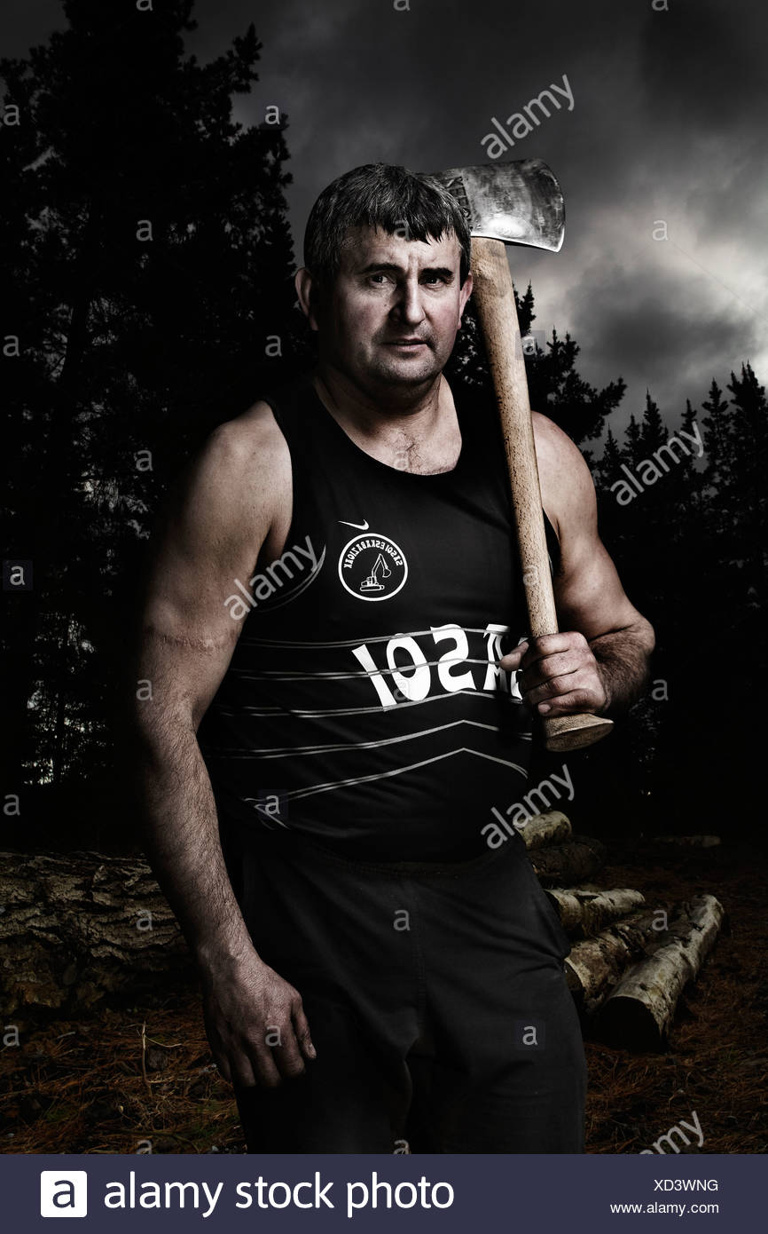 A man stands holding an axe during traditional rural sport training