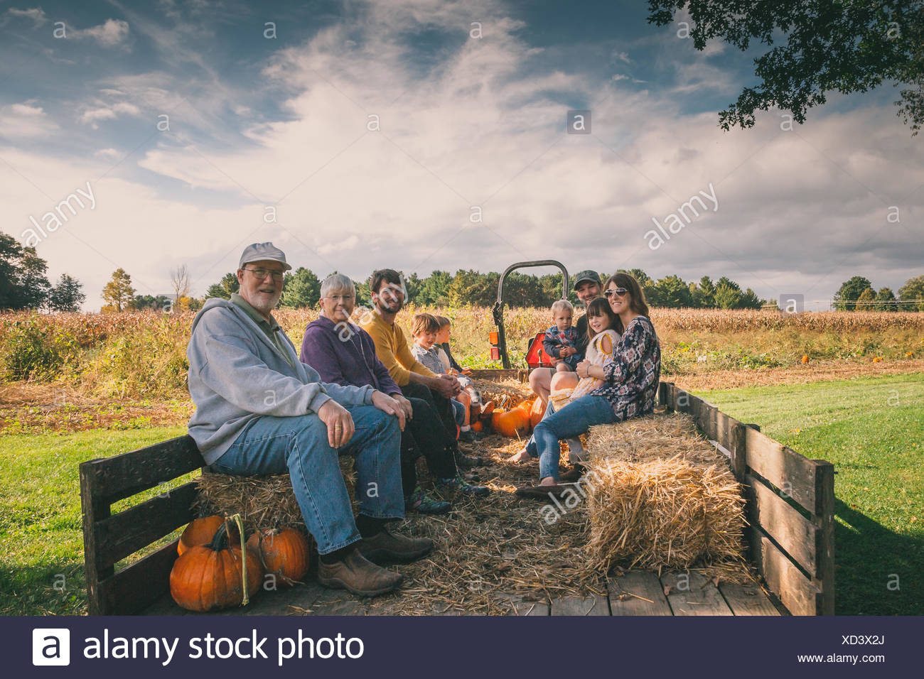 Extended family sitting in a hay wagon at a pumpkin patch Stock Photo
