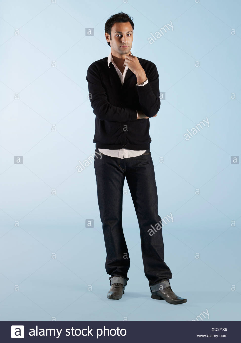 Mid adult man with hand on chin - Stock Image