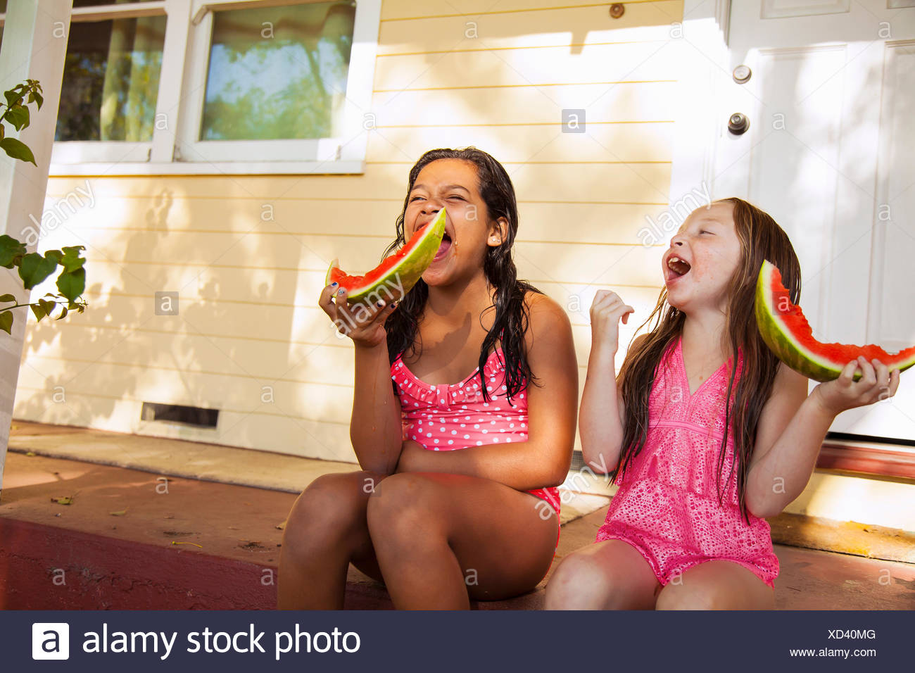 Two laughing girls sitting on house porch with slices of watermelon - Stock Image
