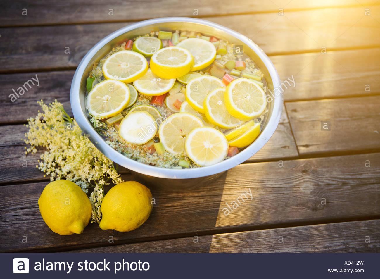 Bowl of elder flower and lemon slices on table - Stock Image