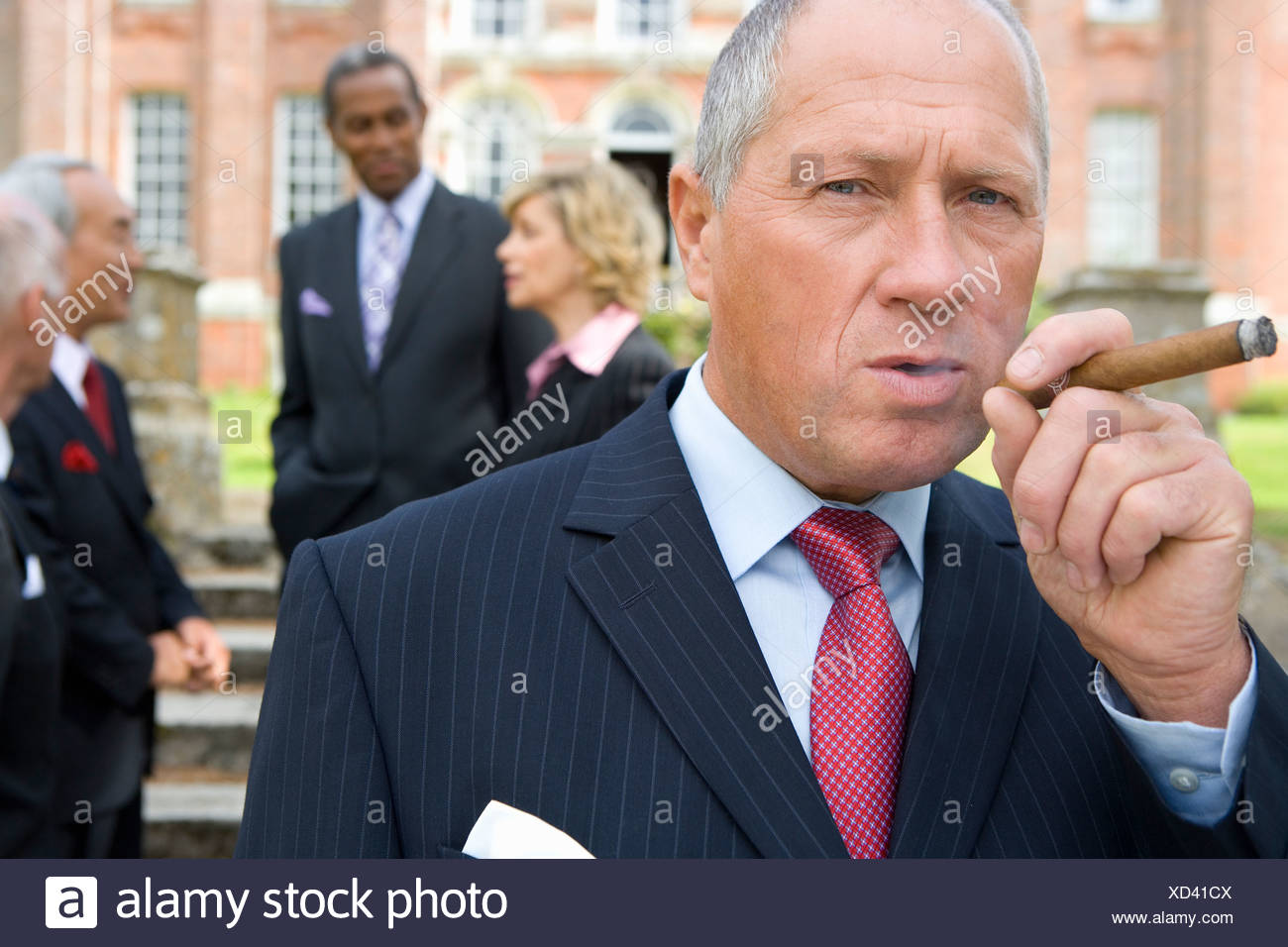 Businessman with cigar by manor house, colleagues in background, portrait Stock Photo