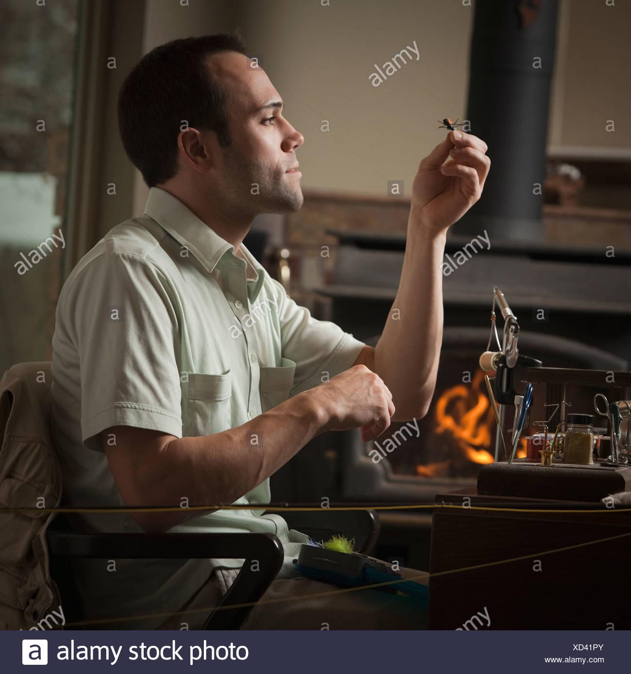 Man looking at fly fishing hook Stock Photo