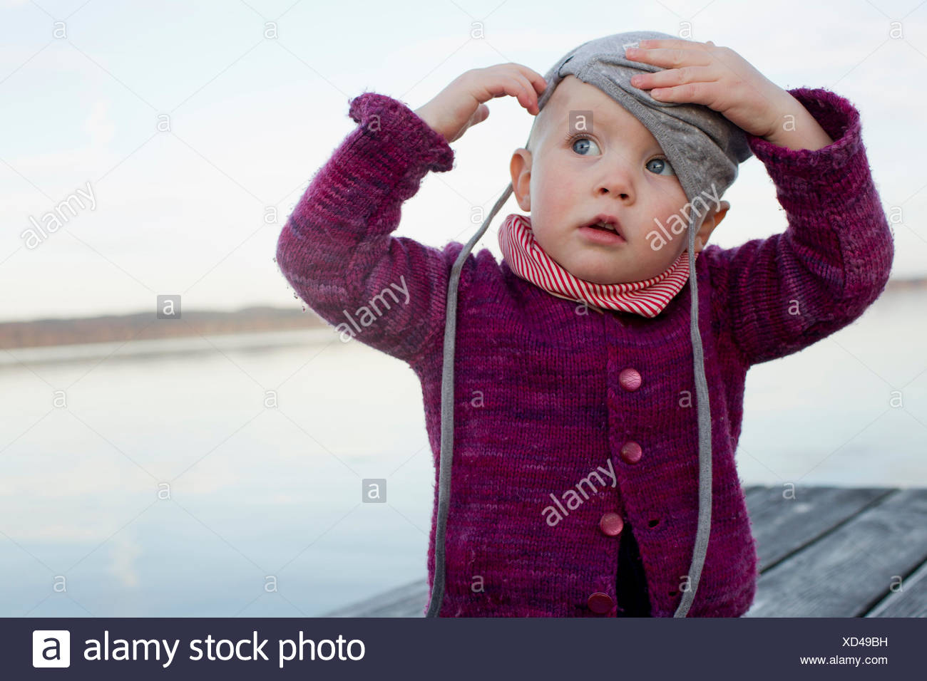 305ac699 Baby girl on lake pier trying to put on hat Stock Photo: 283451605 ...