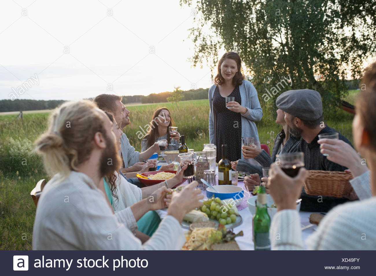 Pregnant woman toasting friends at garden party dinner in rural yard - Stock Image