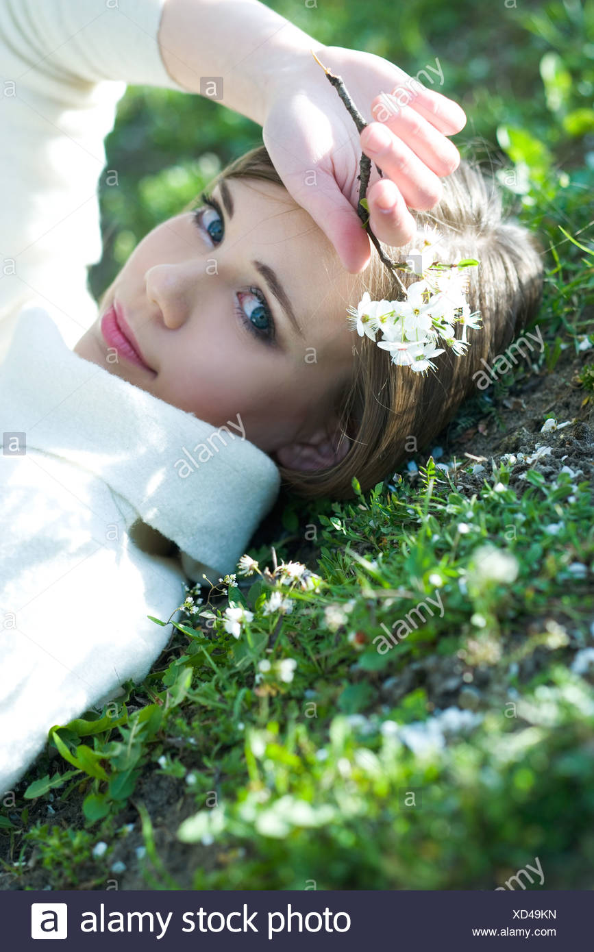 Teenage girl lying on the ground, holding flowers, smiling at camera - Stock Image
