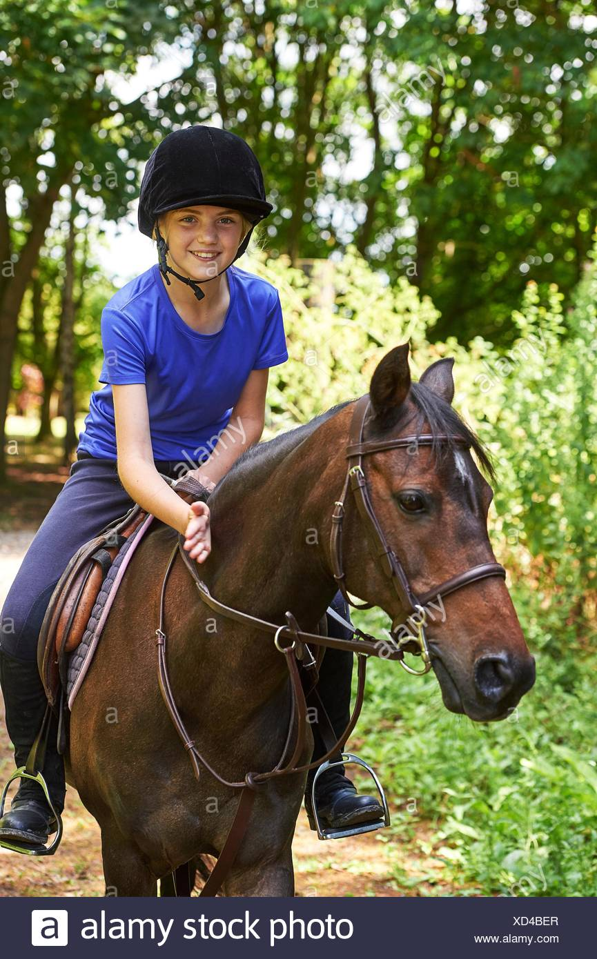 Girl on horse wearing riding hat looking at camera smiling - Stock Image