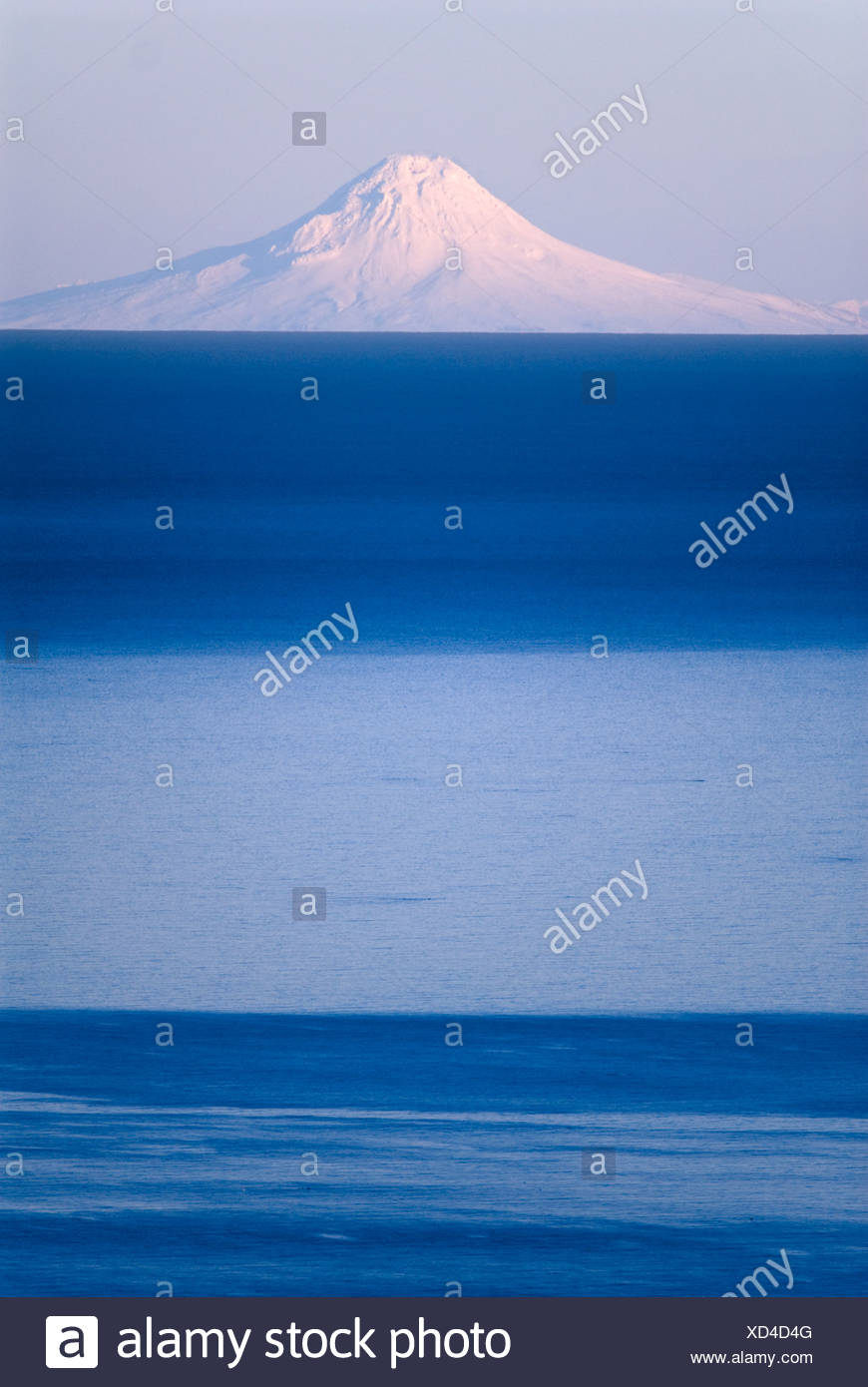 Mt. Augustine seen across Cook Inlet from the Kenai Peninsula in Southcentral Alaska during Winter - Stock Image