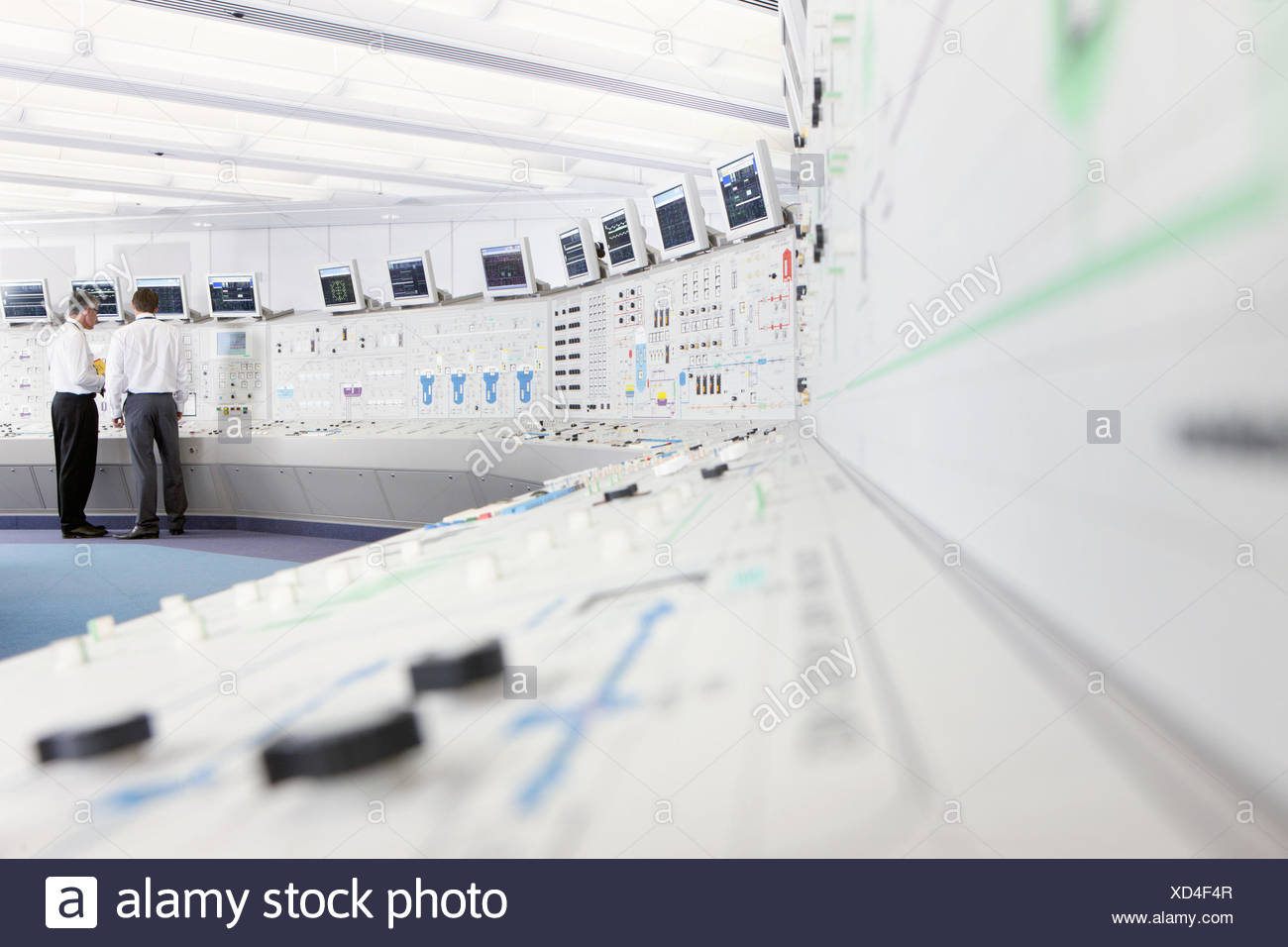 Engineers at control panel in control room of nuclear power station - Stock Image