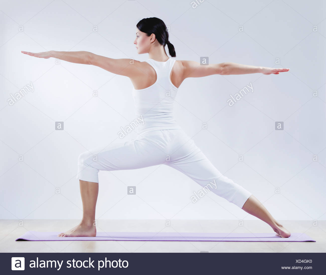 Mid adult woman doing yoga against white background - Stock Image