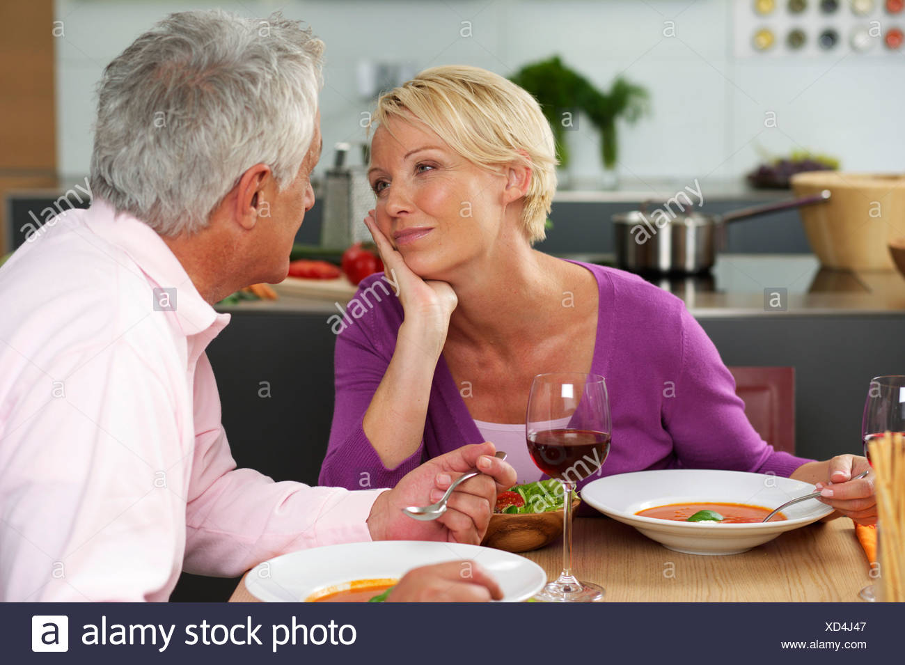 Blonde woman and gray-haired man having dinner, close-up - Stock Image