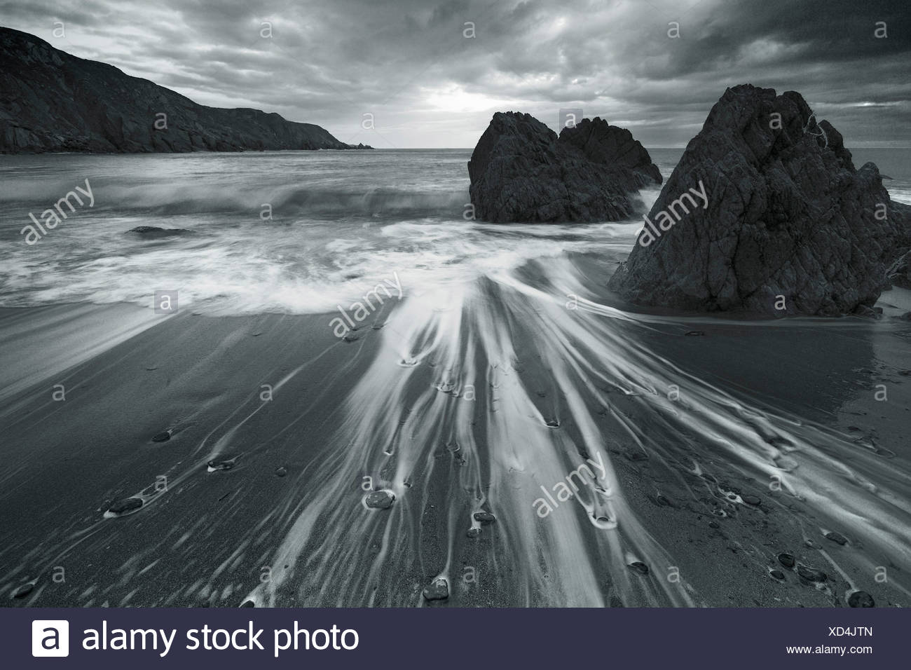 Sea water moving over sand and around rocks on a beach - Stock Image