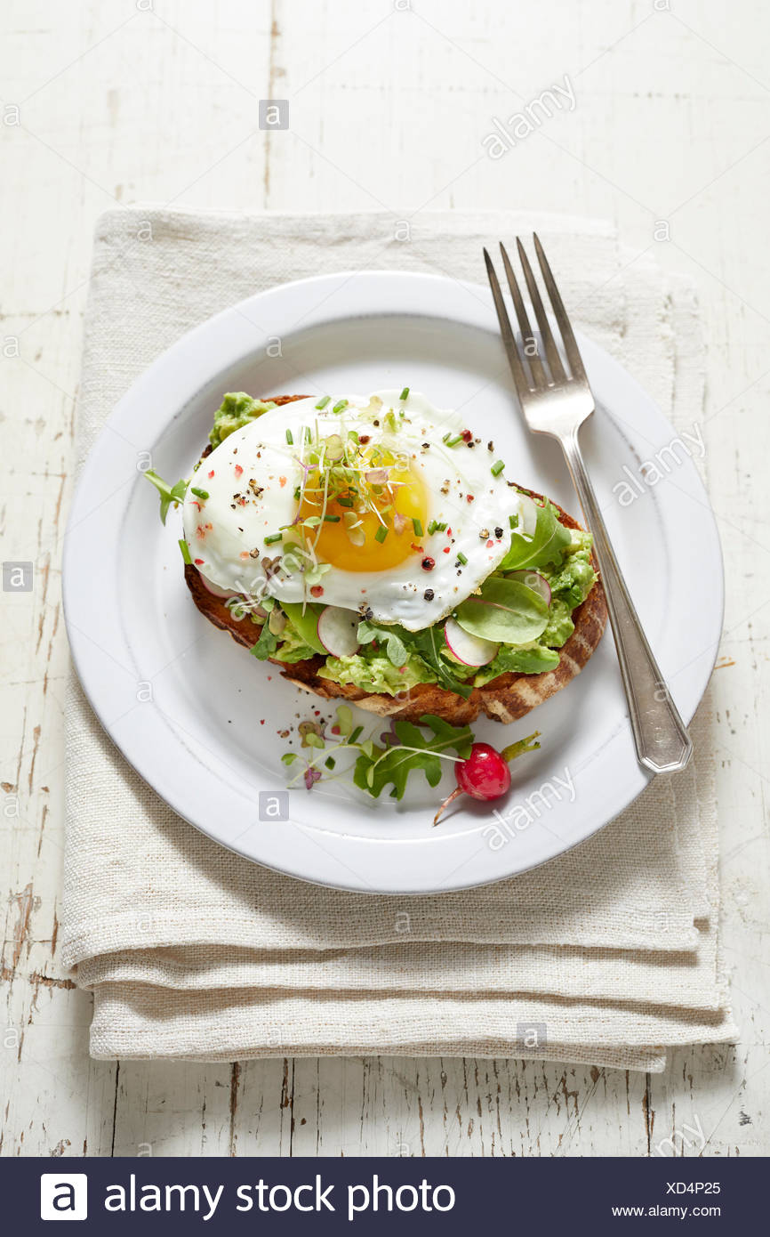Avocado toast with radish, fried egg and micro greens - Stock Image
