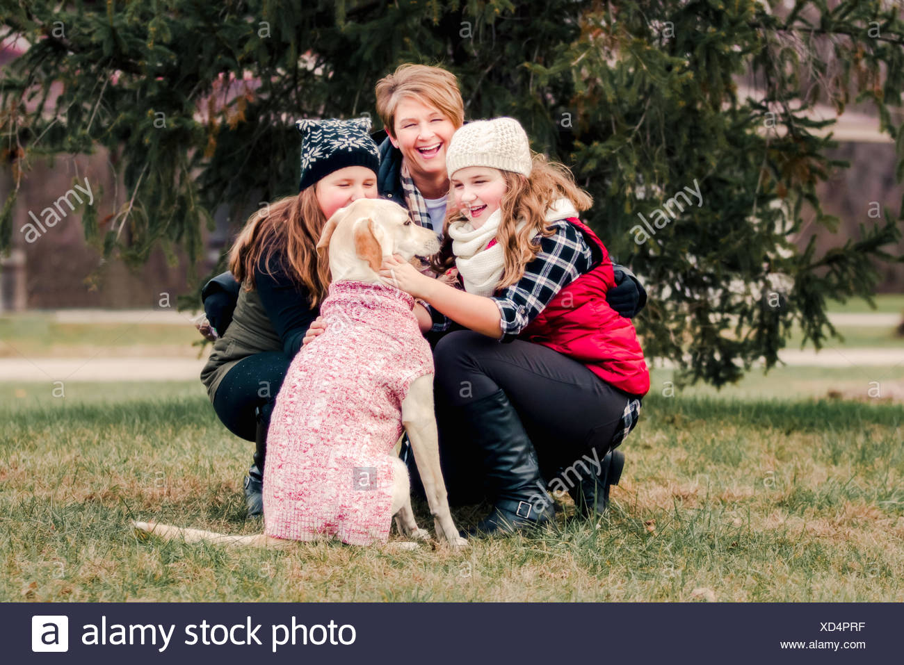 Sisters and their mother crouching to pet dog in garden - Stock Image