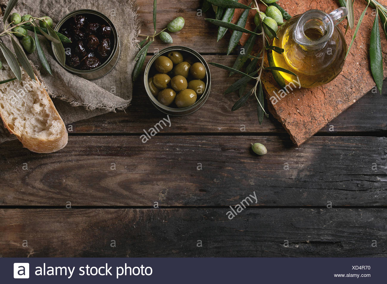 Green and black olives in tin cans with loaf of fresh bread and young olives branch on sackcloth, bottle of olive oil on clay bo - Stock Image