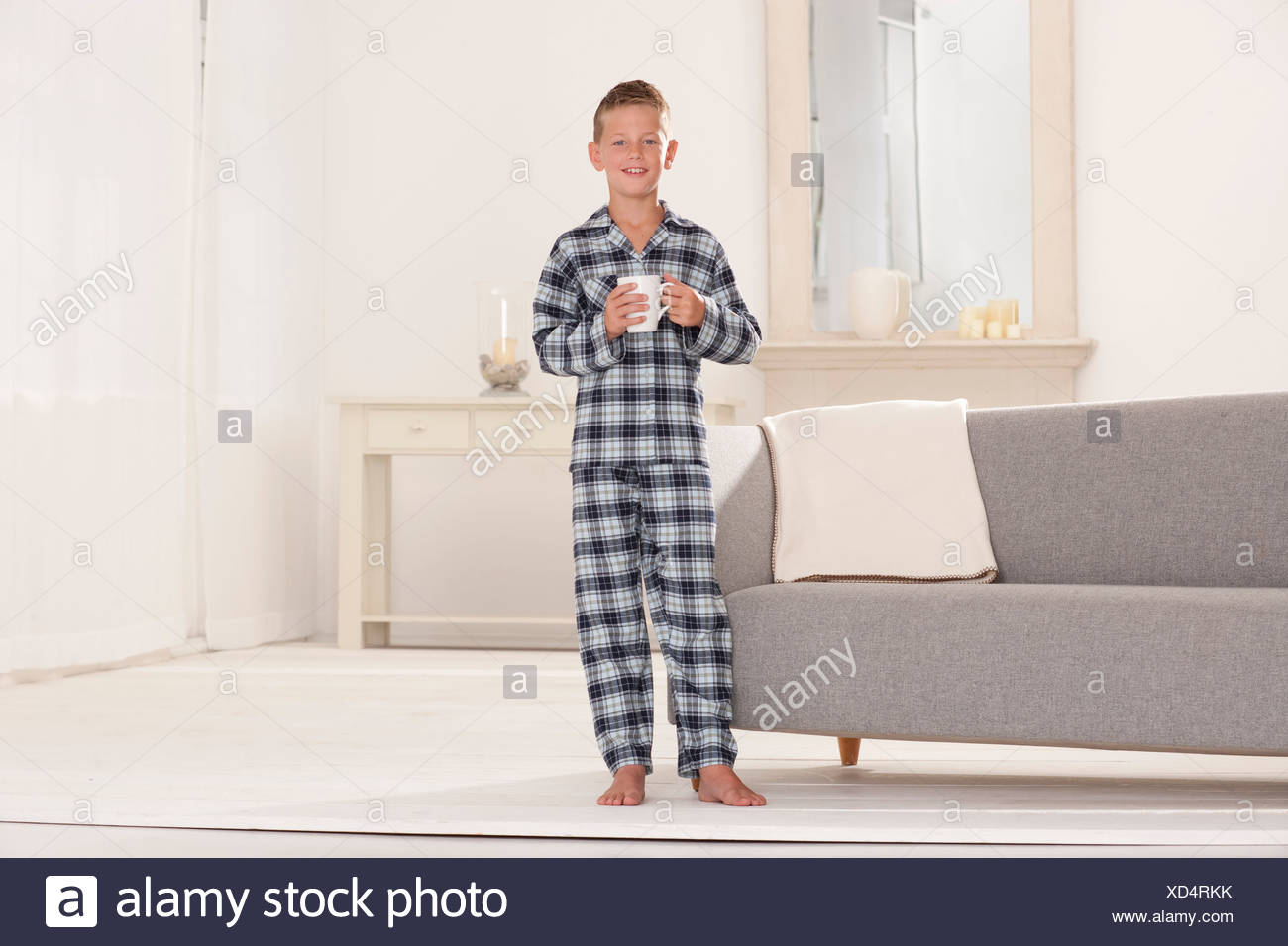 Boy in pajamas with mug in living room - Stock Image