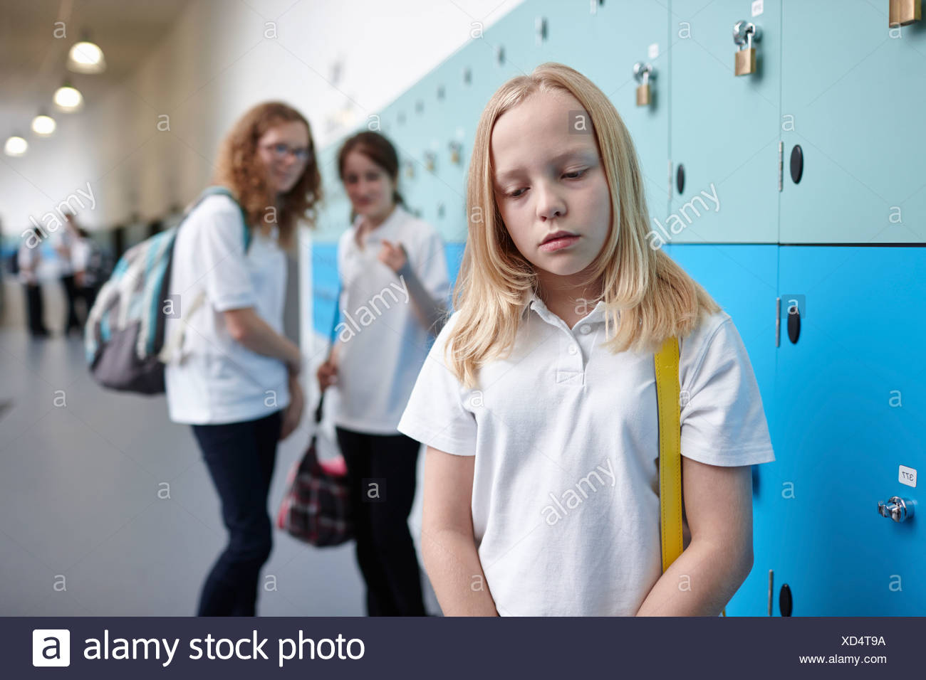 Schoolgirl being bullied in school corridor - Stock Image