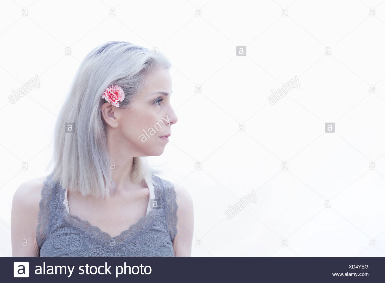 Portrait of mature woman with flower in hair - Stock Image