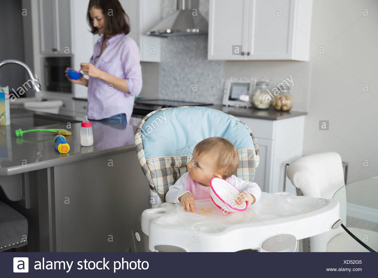 Cute baby girl with mother in kitchen - Stock Image
