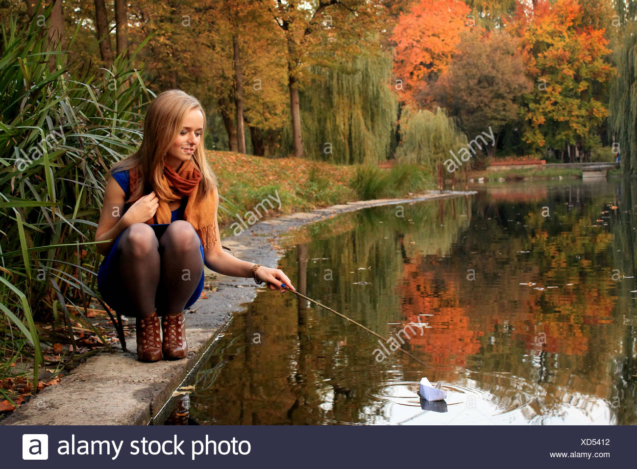 Young woman playing with paper ship on pond - Stock Image
