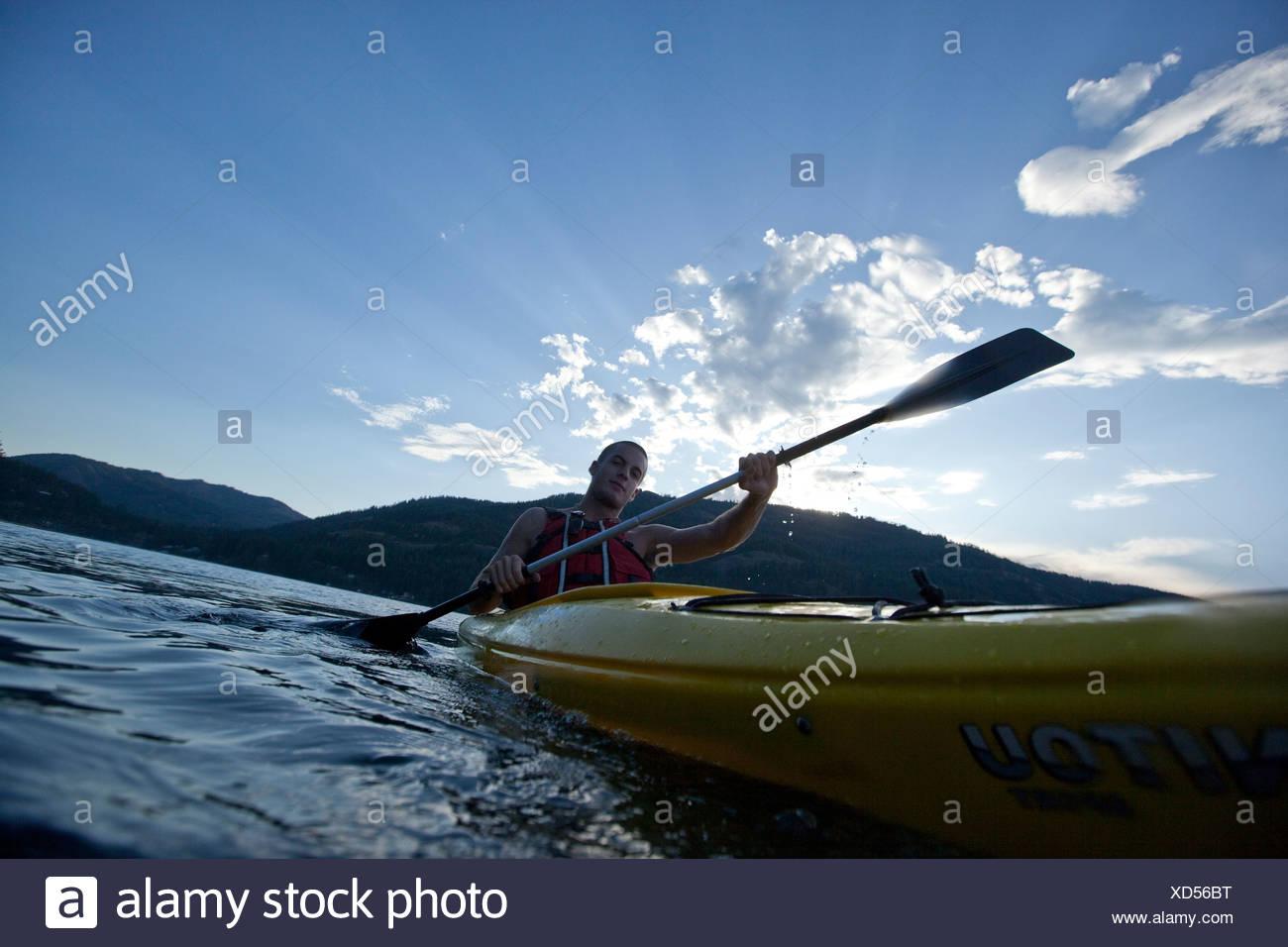 Young man paddles yellow kayak on lake. - Stock Image