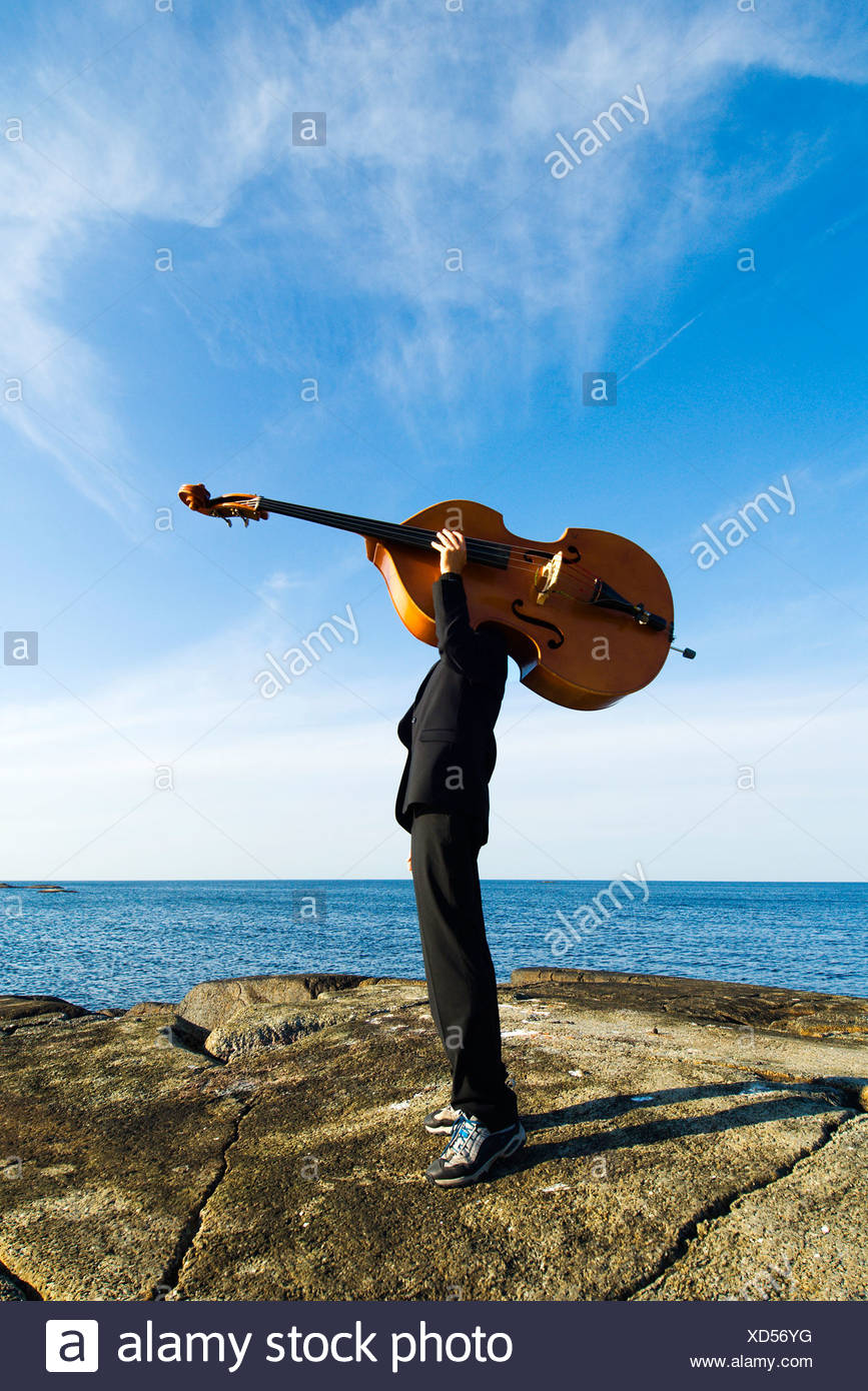 Side view of a jazz musician carrying a contrabass on flat rock against sea and blue sky with clouds - Stock Image