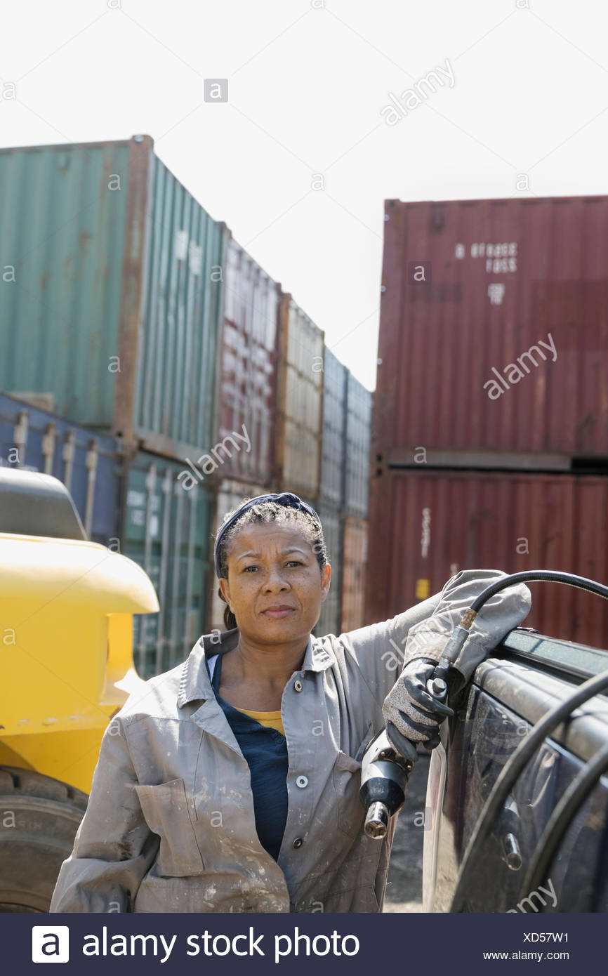 Portrait tough female African American mechanic holding drill, fixing machinery in industrial container yard - Stock Image