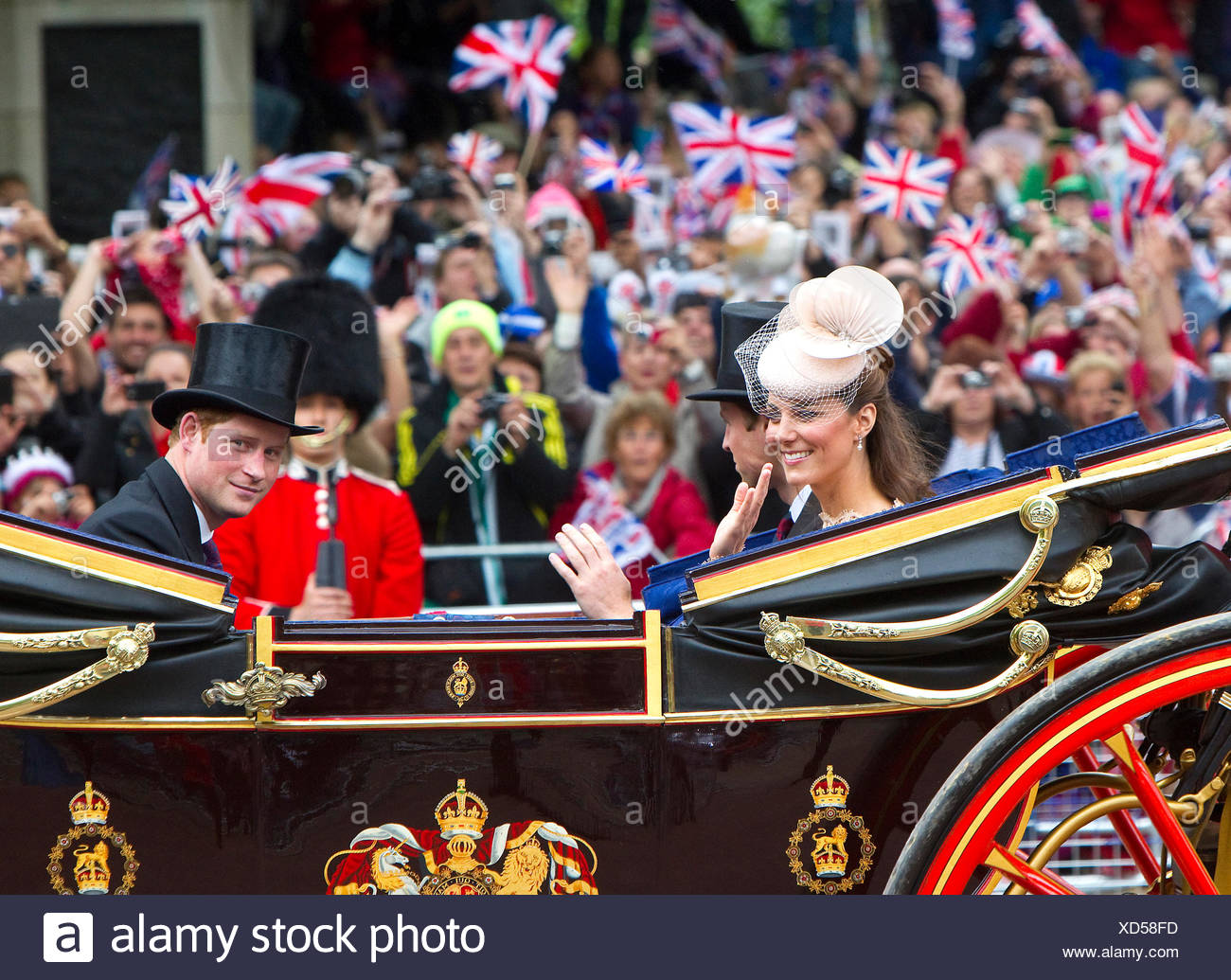The Duchess of Cambridge with Prince William and  Prince Harry, riding down The Mall in an open carriage - Stock Image