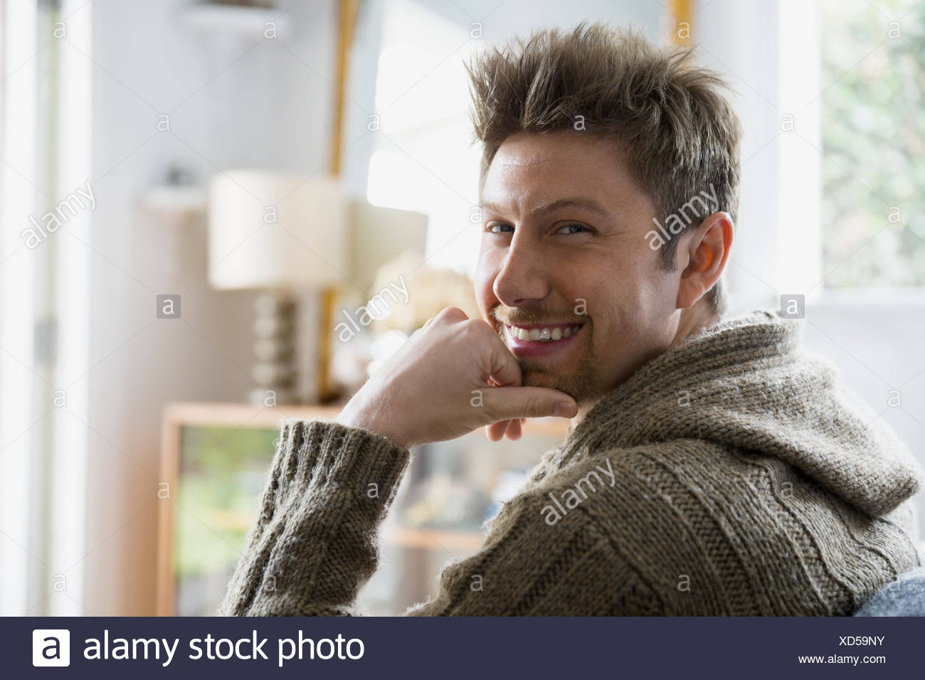 Portrait smiling brunette man with hand on chin - Stock Image