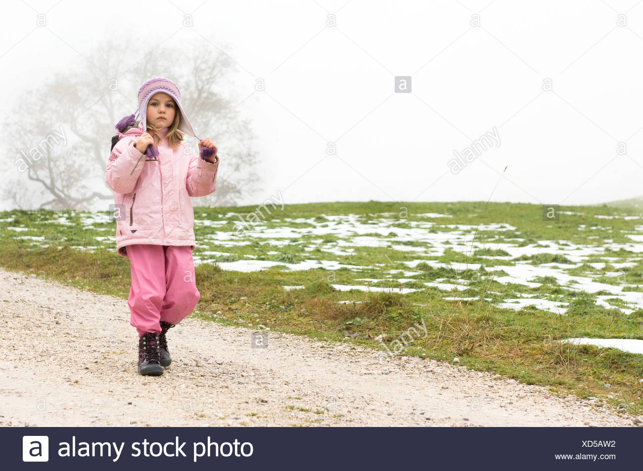 young girl walking on path in winter - Stock Image