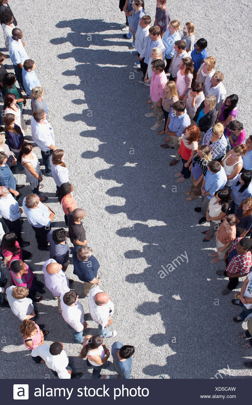 Two groups of people facing one another - Stock Image