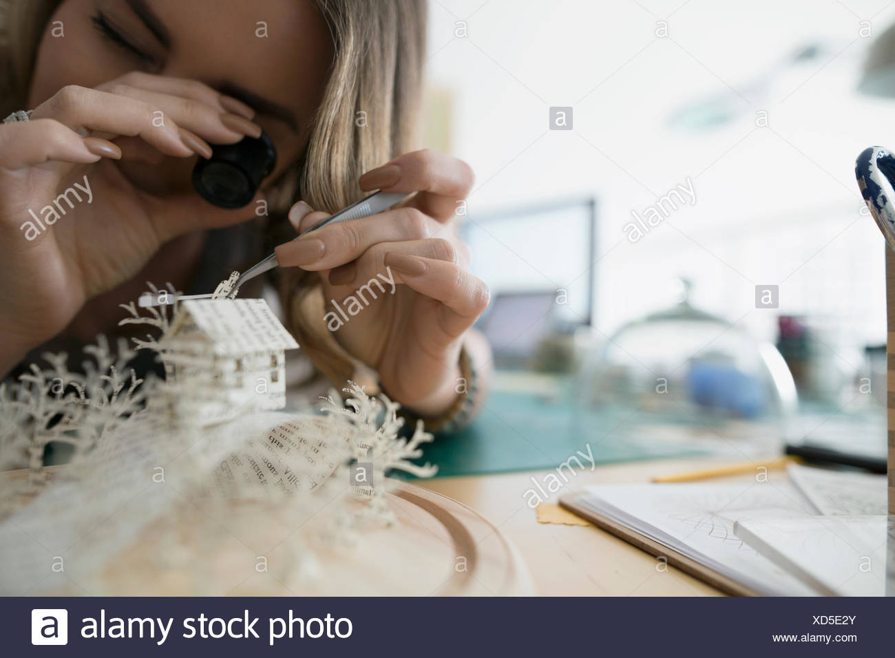 Craftswoman using loupe to assemble paper diorama - Stock Image