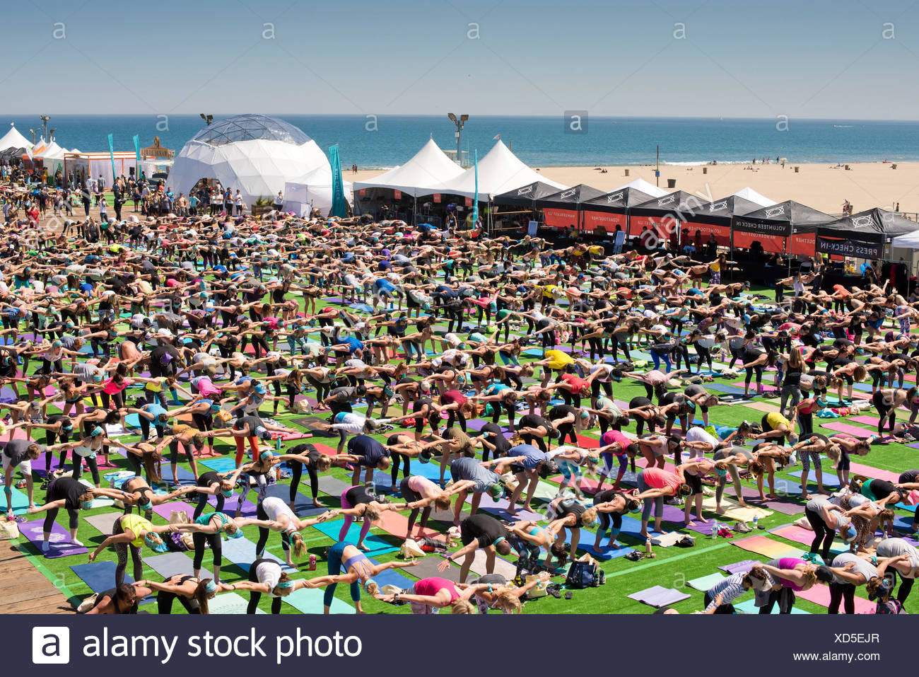 View from above of people stretching during outdoor yoga festival on Santa Monica Pier in Santa Monica, California, USA - Stock Image