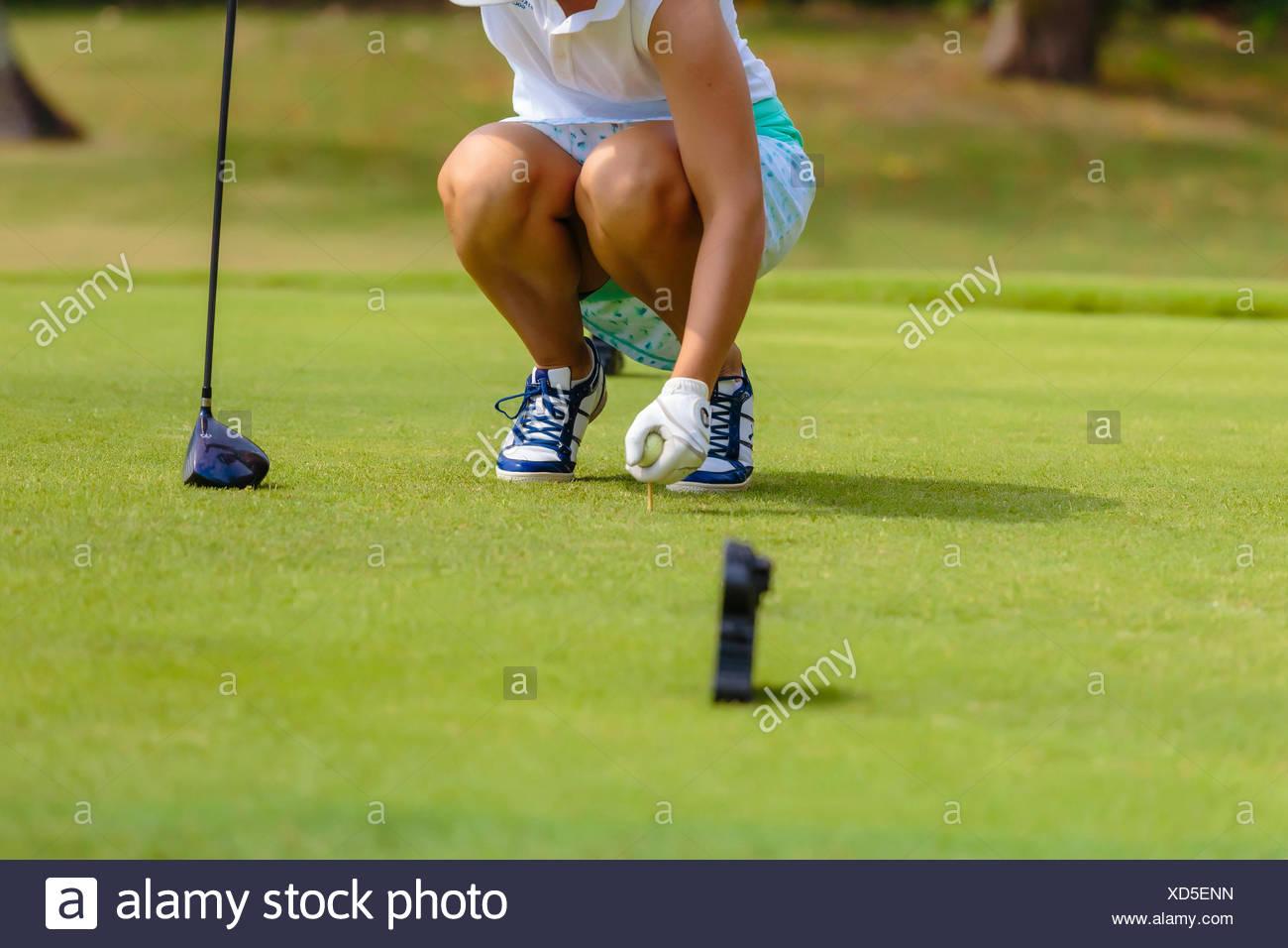 Young woman placing golf ball on tee - Stock Image